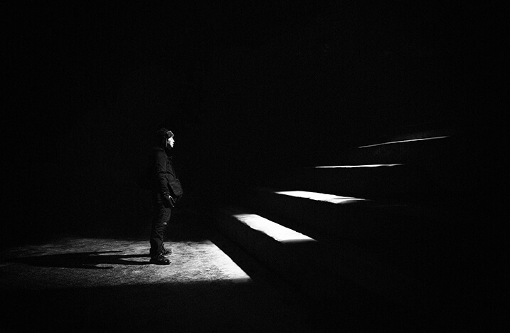 man looking at stairs in the dark