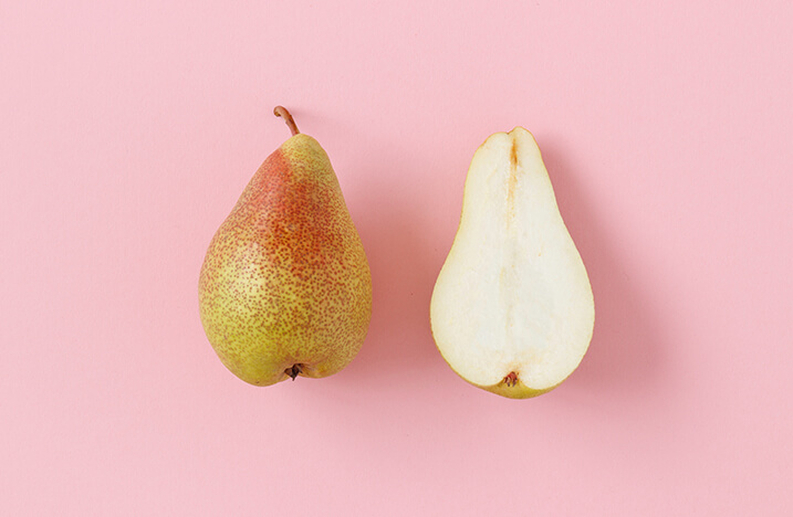 pear in half against pink background