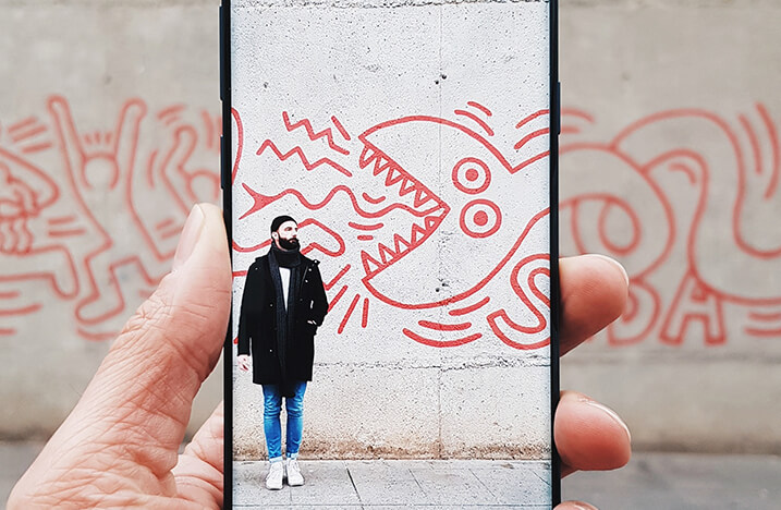 Image of man and graffiti on phone
