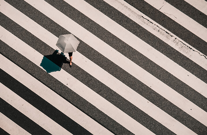 Woman with umbrella crossing road thumbnail